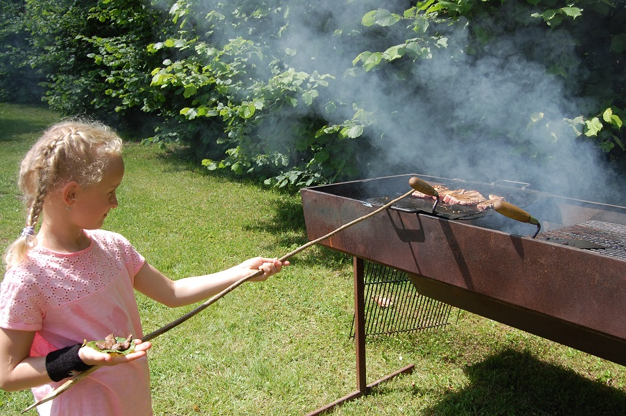 Pige laver mad over grill